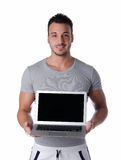 Handsome young man smiling and showing laptop computer Royalty Free Stock Photos