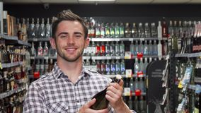 Handsome young man smiling to the camera while choosing wine. Young handsome man examining wine bottle at the supermarket while doing groceries. Attractive royalty free stock images