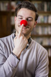 Handsome young man smiling and touching red clown nose. Standing in a living room Stock Photography