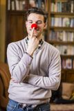 Handsome young man smiling and touching red clown nose. Standing in a living room Royalty Free Stock Photos