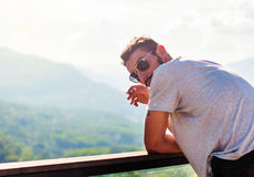 A handsome young man smokes with a view of the mountains. A young handsome man in sunglasses smokes with a view of the high mountains while traveling Stock Photography