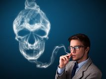 Young man smoking dangerous cigarette with toxic skull smoke. Handsome young man smoking dangerous cigarette with toxic skull smoke royalty free stock images