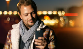 Handsome young man sms texting using app on smart phone at autum. /summer sunset in city. Using smartphone smiling happy wearing urban hipster outfit outdoors Stock Photo