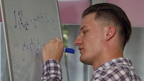 Handsome young man solving math problem on whiteboard. Attractive male student smiling to the camera while solving algebra equation on whiteboard at classroom stock video