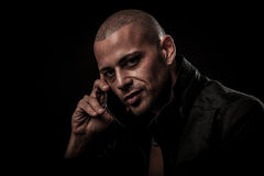 Handsome young man speaking on cell phone in darkness to transfe Royalty Free Stock Images