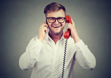 Cheerful man comparing old and new technology. Handsome young man speaking at once on old-fashioned red phone and new smartphone being busy Royalty Free Stock Images