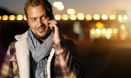 Handsome young man speaking on smart phone at autumn sunset in c. Ity. Using smartphone for a phone call, smiling happy wearing urban hipster outfit outdoors at Stock Photography