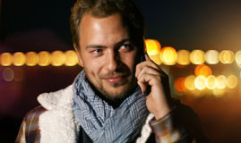 Handsome young man speaking on smart phone at autumn sunset in c Royalty Free Stock Photography