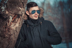 A handsome young man with spectacles in the Park. In winter Royalty Free Stock Images