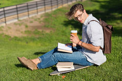 Young man in spectacles reading book and drinking coffee while sitting on skateboard in park Stock Photos