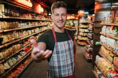 Handsome young man stand in grocery store among pasta shelfs. He reach hand to camera and smile. Handsome young man stand in grocery store among pasta shelfs stock image