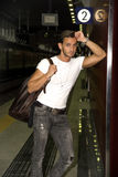Handsome young man standing against wall in train or subway station Stock Photos