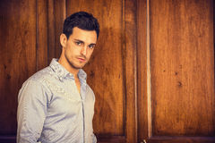 Handsome young man standing against wardrobe. Sexy handsome young man standing wearing shirt in his bedroom against wooden wardrobe door Royalty Free Stock Photo