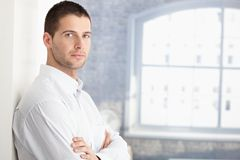 Handsome young man standing arms crossed Stock Photos