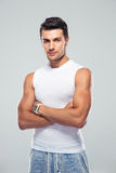 Handsome young man standing with arms folded Royalty Free Stock Images