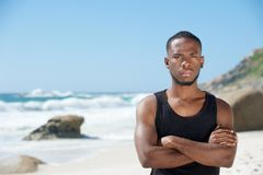 Handsome young man standing at the beach with arms crossed Royalty Free Stock Photography