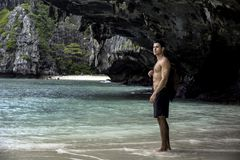 Young man standing on beach by the ocean stock photo