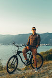 Handsome Young Man Standing With Bike On Coast And Enjoying View of Nature Sunset Vacation Traveling Relaxation Resting Concept. Handsome young man cyclist with Royalty Free Stock Image