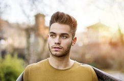 Handsome young man standing in city park Royalty Free Stock Photography