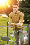 Handsome young man standing in city park Stock Images