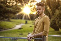 Handsome young man standing in city park Stock Photo