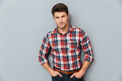 Handsome young man standing with hands in pockets. Over gray background Stock Photography