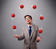 Young man standing and juggling with red balls Stock Images