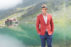 Handsome young man standing near a lake Stock Photography