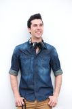 Handsome young man standing outdoors with a pair of headphones Royalty Free Stock Images