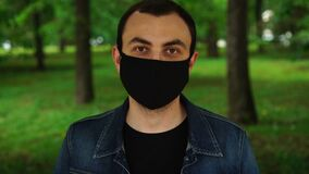Handsome young man standing outdoors and put on medical mask to protect others from virus spread