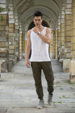 Handsome young man standing outdoors under old colonnade. In european town royalty free stock image