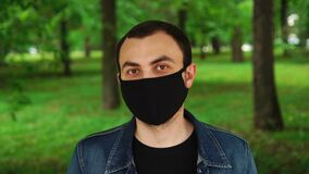 Handsome young man standing outdoors wearing black mask to protect others from virus spread