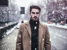 Young man in snowy city stock photos