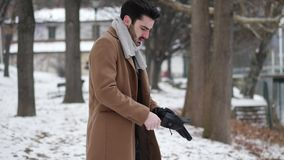 Young man in snowy city putting on gloves. Handsome young man standing outside in winter, in snowy Turin, in Italy, on river docks, putting on leather gloves stock video footage