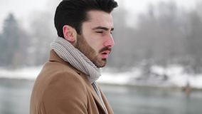 Young man in snowy city in Italy. Handsome young man standing outside in winter, in snowy Turin, in Italy, on river docks stock footage