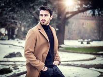 Young man in snowy city in Italy. Handsome young man standing outside in winter, in snowy Turin, in Italy, in urban setting Royalty Free Stock Images