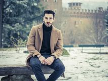 Young man in snowy city in Italy. Handsome young man standing outside in winter, in snowy Turin, in Italy, in urban setting Stock Images