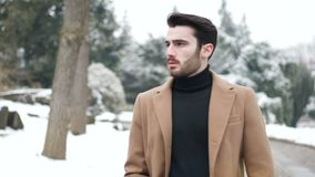 Young man in snowy city in Italy. Handsome young man standing outside in winter, in snowy Turin, in Italy, in urban setting stock footage