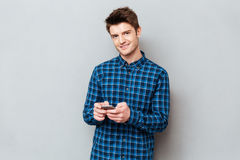 Handsome young man standing over grey wall and chatting stock photography