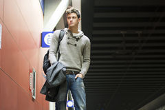 Handsome young man standing in train or subway station Royalty Free Stock Photography