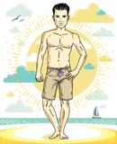 Handsome young man standing on tropical beach in bright shorts. Royalty Free Stock Images