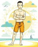 Handsome young man standing on tropical beach in bright shorts. Stock Photo