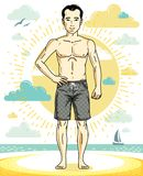Handsome young man standing on tropical beach in bright shorts. Royalty Free Stock Image