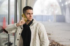 Handsome young man standing using a mobile phone Stock Photos