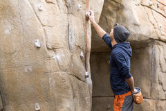 Handsome young man starting to climb on natural rocky wall. Royalty Free Stock Images