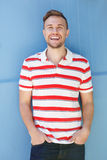 Handsome young man in striped shirt laughing against blue wall Stock Images