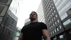 Young man stands proudly against the background of a modern building. A handsome young man with strong muscles stands proudly against the background of a modern stock video footage