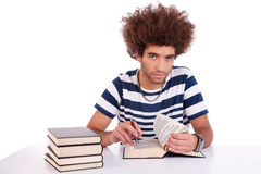 Handsome young man studying and reading a book on Stock Photos