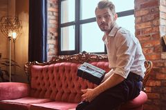 A handsome young man with a stylish beard and hair elegantly dressed holding a gift box while sitting on a red vintage stock photography