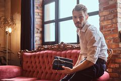 A handsome young man with a stylish beard and hair elegantly dressed holding a gift box while sitting on a red vintage stock image